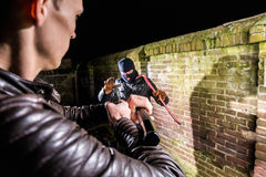 Policeman aiming torch and pistol towards busted scared cracksma. Policeman Aiming Pistol Towards Scared Cracksman At Night royalty free stock photography
