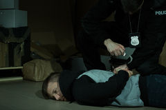 Policeman arresting an offender Stock Photos