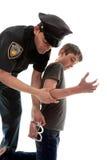 Policeman arresting teen criminal Royalty Free Stock Photography