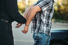 Policeman arrests the car thief on road. Cop at the work. Law protection concept, professional safety control stock images