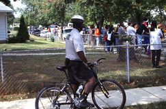 A policeman on a bicycle watches a group of teenegers that is gathering. A policeman on a bicycle watches a group of teenagers that have gathered near an royalty free stock photos