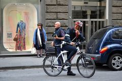 Policeman with bike. Street shot in Florence, Italy. People are waiting and looking in the same direction, the policeman seems to be rather puzzled stock photography