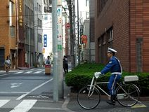 Policeman on bike. A Japanese policeman on a bicycle stopping at a crossing stock image