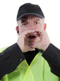 Policeman calling out. Policeman wearing yellow reflective safety vest holding hands around his mouth and calling out Royalty Free Stock Photo