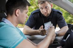 Policeman checking documents. Policeman checking young male driver's documents stock photos