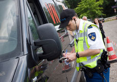 Policeman is checking driving license. HAAKSBERGEN, NETHERLANDS - JUNE 09: A policeman is checking the driving license of a car driver during a massive traffic Stock Images