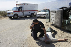 Policeman Checking Pulse Of Car Crash Victim Stock Photo