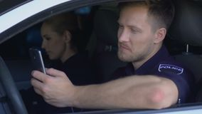 Policeman checking social media while patrolling with partner in car, addiction. Stock footage stock footage