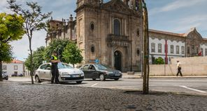 Policeman checks and writes a traffic ticket. Braga, Portugal - May 23, 2018: policeman checks and writes a traffic ticket on a car in the city center on a Stock Photo