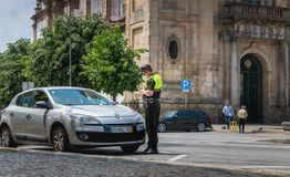 Policeman checks and writes a traffic ticket. Braga, Portugal - May 23, 2018: policeman checks and writes a traffic ticket on a car in the city center on a Stock Photography