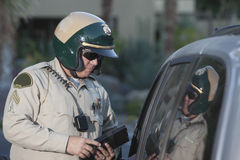 Policeman With Clipboard Standing By Car Royalty Free Stock Photography