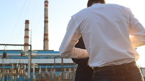 The policeman detains the chief inspector when taking bribes, arrest, corruption, against power plant background. Sunset stock footage