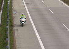 Policeman drives motorbike on highway in sunny day Royalty Free Stock Image