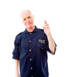 Policeman with finger crossed for luck Royalty Free Stock Image