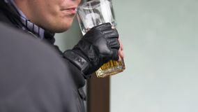 Policeman in fingerless gloves and leather jacket drinking a glass of beer. Stock footage stock video footage