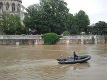 A policeman floats on a boat on a brown river. Europe. France. Flood in Paris. Seine river near Notre Dame de Paris. stock images