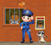 A policeman in front of a jail with two cats Stock Images