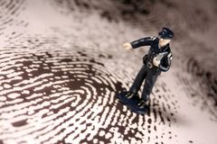 Policeman on giant fingerprint Stock Photos