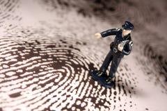 Policeman on giant fingerprint. A miniature figure policeman points to a giant fingerprint Stock Photos