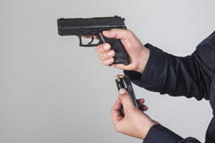 Policeman with gun. Policeman reloaded his gun with bullets Royalty Free Stock Photography