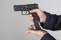 Policeman with gun. Policeman reloaded his gun with bullets Stock Images