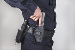 Policeman with gun. Policeman take off his gun from zone Stock Photos