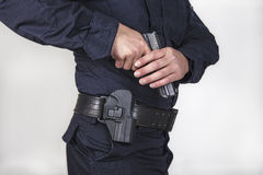 Policeman with gun. Policeman taking off his gun from the zone Royalty Free Stock Images