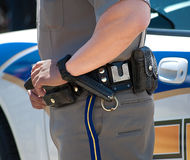 Policeman with hand on gun belt Royalty Free Stock Image