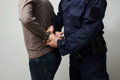 Policeman handcuffing an illigal man. Stock Image