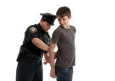 Policeman handcuffing teenager Royalty Free Stock Photo