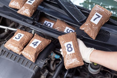 Policeman holding drug package found in engine compartment of a car. Police officer holding drug package discovered in engine compartment of a car Royalty Free Stock Photos