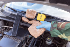 Policeman holding drug package found in engine compartment of a. Police officer holding drug package discovered in engine compartment of a car Stock Photography