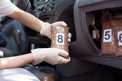Policeman holding drug package found in secret compartment in a car. Police officer holding drug package found in secret compartment in a car Royalty Free Stock Images