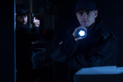 Policeman holding flashlight. Photo of a young policeman holding flashlight during action royalty free stock image