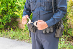Policeman Holding Handcuffs. Detail of law enforcement officer in blue uniform and belt with radio and weapon holding handcuffs stock photo