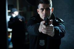 Policeman holding a handgun. Image of a confident handsome policeman holding a handgun royalty free stock photo