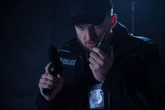 Policeman holding radio and gun Royalty Free Stock Photos