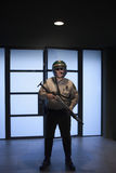Policeman Holding Rifle Against Door Royalty Free Stock Photography
