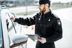 Policeman knocking at the car window stock photography