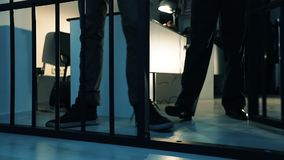 A policeman leads a criminal into the prison cell. Close-up of a foot. Slow motion stock footage