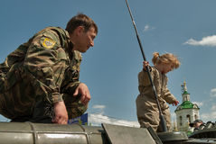 Policeman and little girl on armoured carrier Stock Images