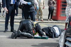 The policeman of London renders first aid to the pedestrian who suffered in the accident.  Stock Photo