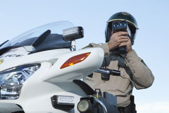 Policeman Monitoring Speed Through Radar Against Sky Stock Photography