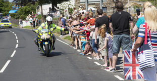 Policeman on motorbike. Olympic torch relay 26 May 2012 Bryncethin Bridgend UK Police man riding on a motorbike with hands outstretched to touch the crowds hands stock photos