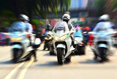 Policeman on motorcycle escorting government officials Royalty Free Stock Images