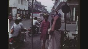 Policeman On Motorcycle. INDONESIA, BALI DENPASAR, FEBRUARY 1977. Busy, Crowded Gajah Mada Main Street Intersection, With A Policeman On A Scooter And Two Girls stock video