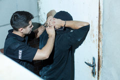 Policeman overpowering kidnapper. Horizontal photo of policeman overpowering masked kidnapper royalty free stock image