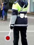 Policeman with the paddle while directing traffic. In the big city Royalty Free Stock Photography