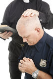 Policeman in Prayer. Policeman prays and receives a blessing from his priest or minister Stock Images