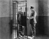 Policeman and prisoner in a jail cell Stock Images